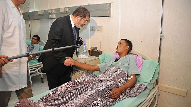 Egyptian President Mohamed Morsi (L) shakes hands with an Egyptian soldier who was wounded in an attack in Sinai during a visit to soldiers at a hospital in Cairo, August 7, 2012.